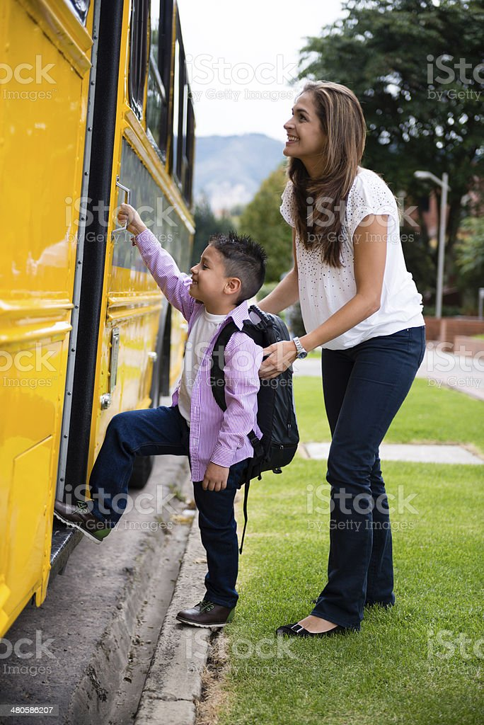 Boy taking the school bus stock photo