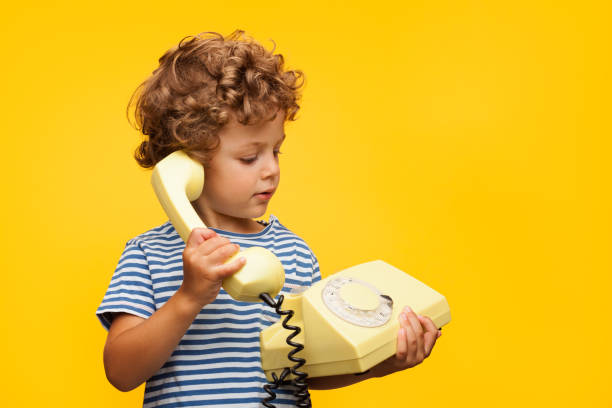 boy talking obsolete phone - kids phones stock photos and pictures