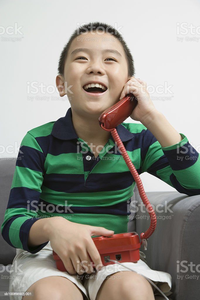 Boy (8-9) talking on telephone, smiling foto de stock libre de derechos