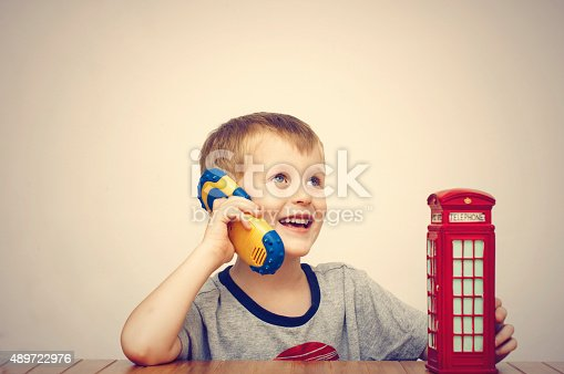 Boy talking on the phone and vintage british red telephone booth