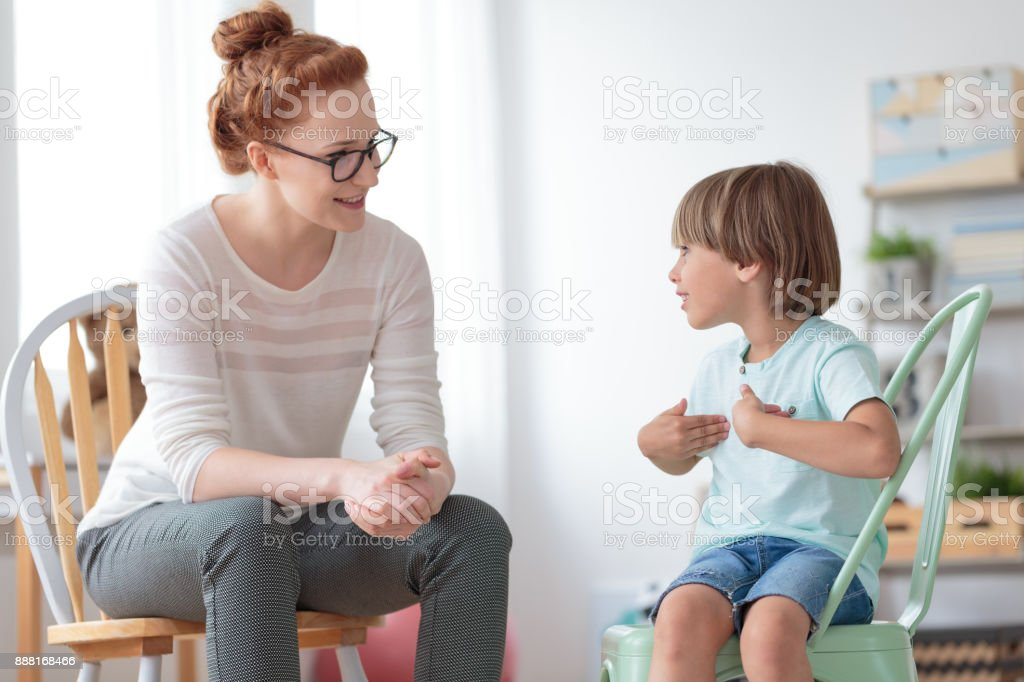 Boy talking with child psychotherapist stock photo