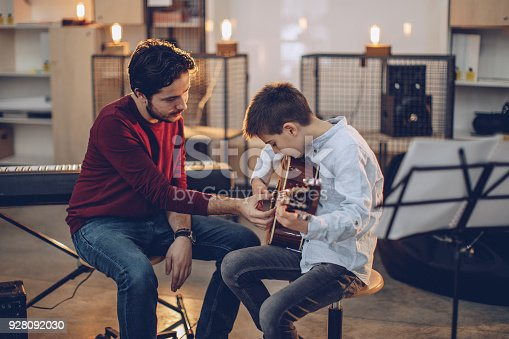 istock Boy teaching to play guitar in music school 928092030