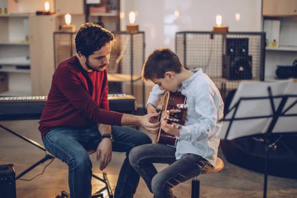 指導音楽学校でギターを弾く少年 - 美術の授業 ストックフォトと画像