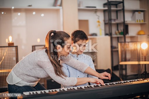 Boy teaching to play synthesizer in music school