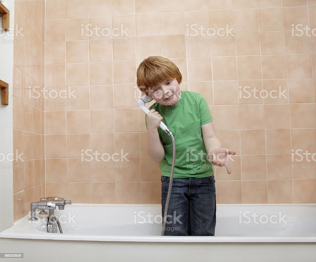 boy telephoning with showerhead in bathtub royalty-free stock photo