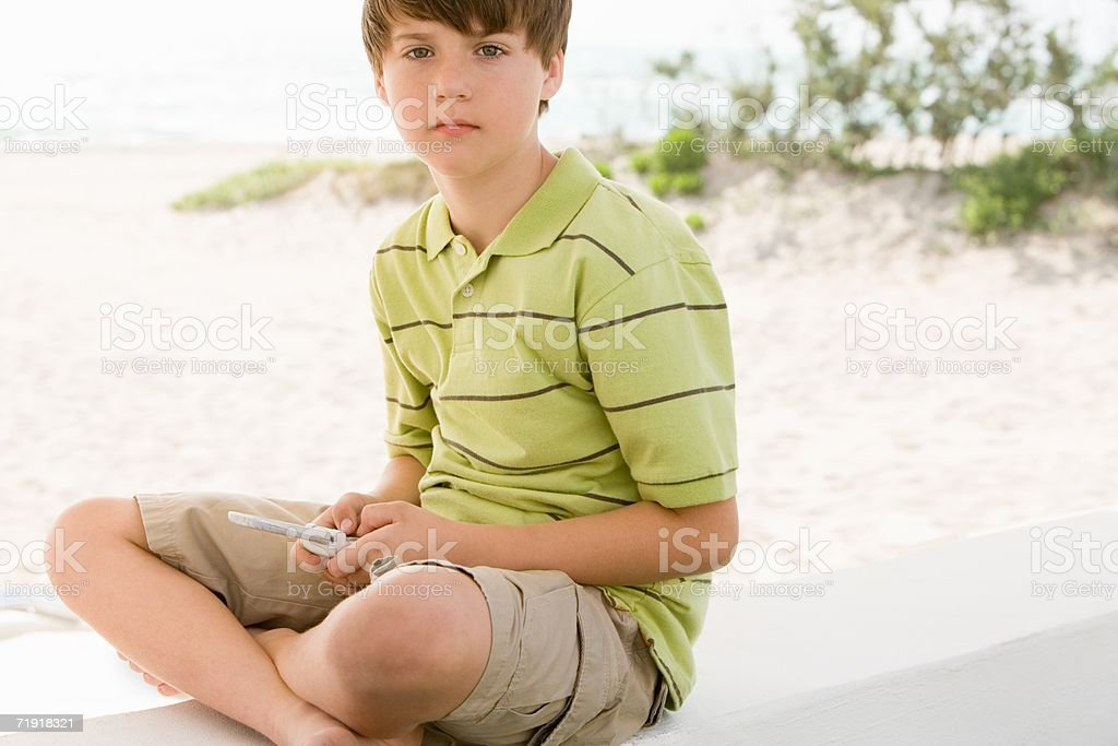 Boy texting by the beach royalty-free stock photo