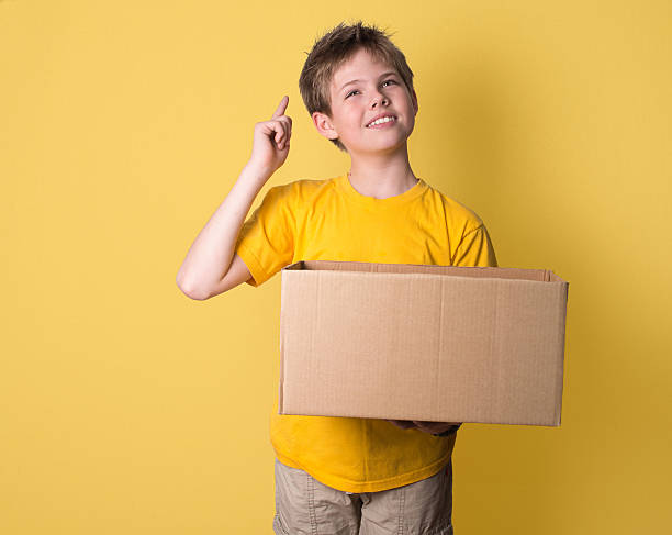 Boy thinking holding box. Think out of the box concept. – Foto