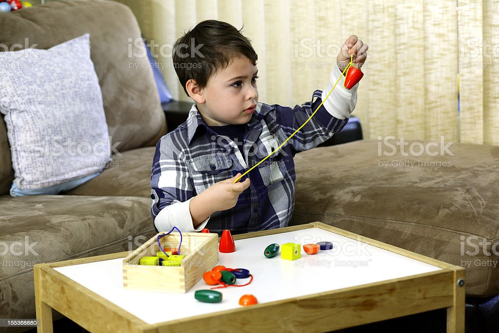 Boy threading a string of beads stock photo