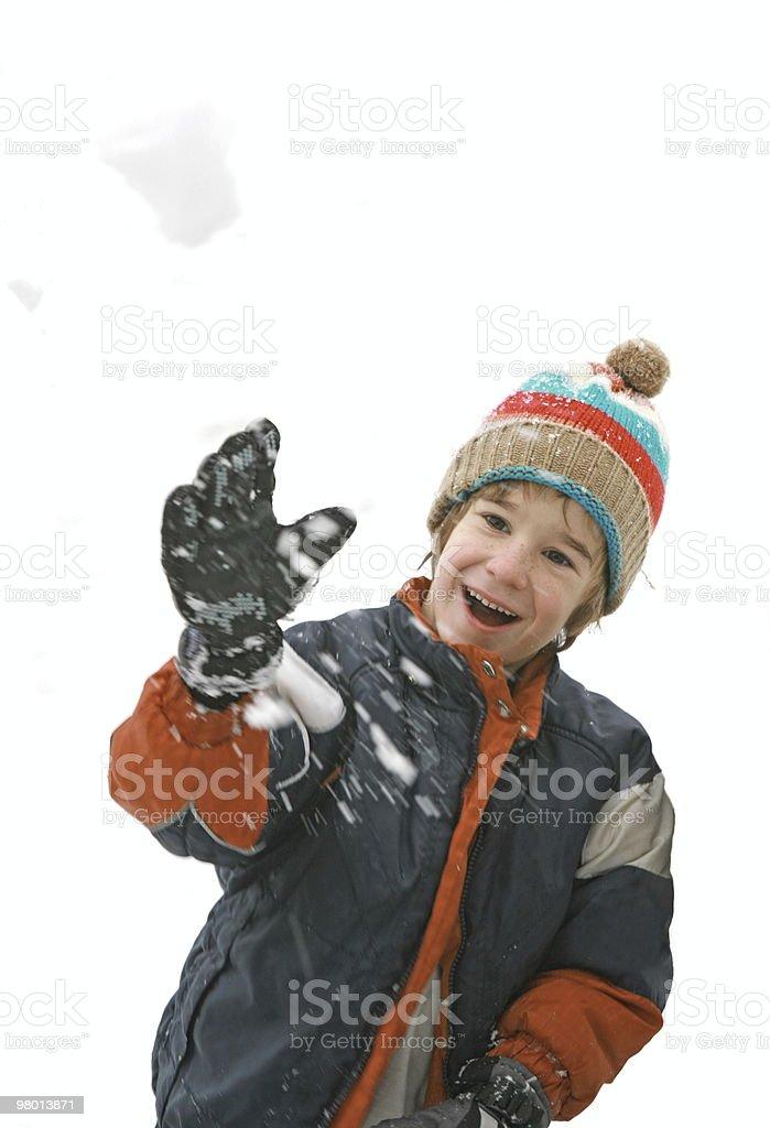 Menino jogando uma bola de neve foto royalty-free