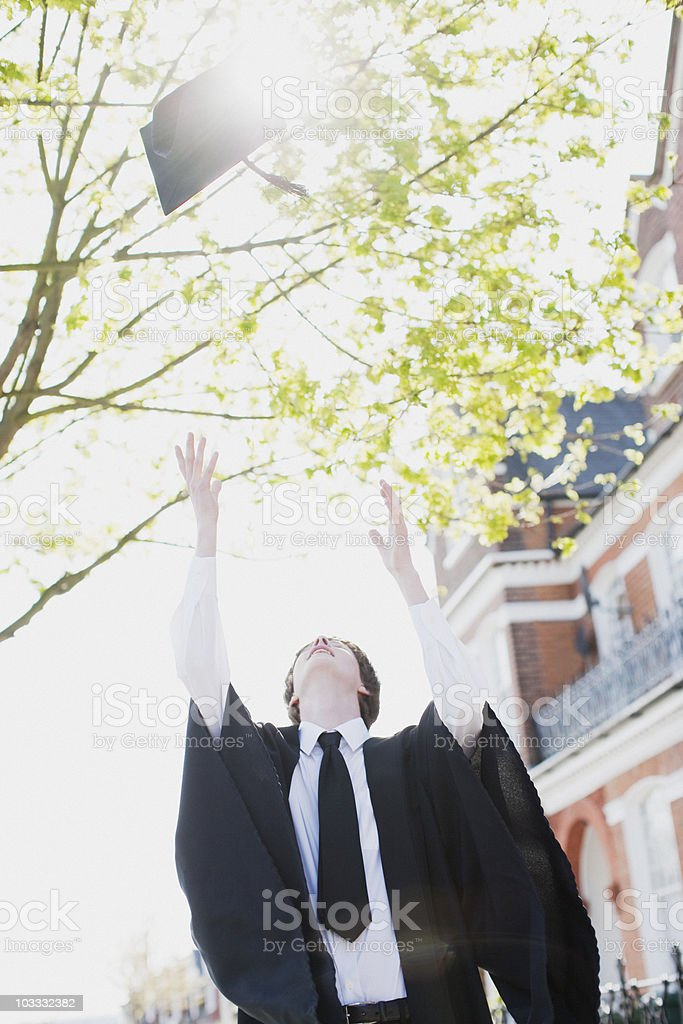 Boy throwing mortarboard overhead stock photo