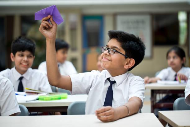 Junge werfen Papierflugzeug in den Klassenraum – Foto