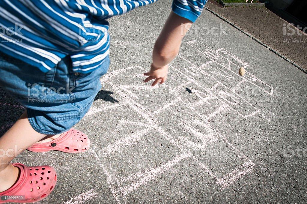 boy throwing stone on hopscotch stock photo