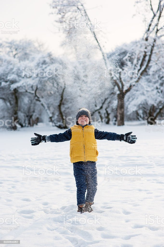 Boy throws up snow and spreads his arms to  sides stock photo
