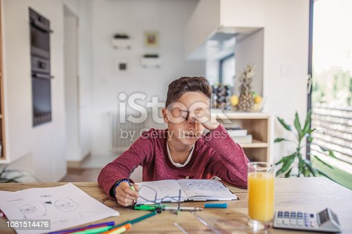 One man, young boy is tired of doing homework, sitting at the table.