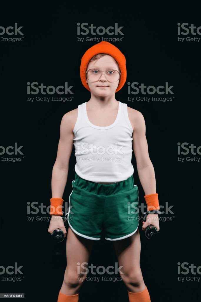 niño de entrenamiento con pesas aisladas en negro. concepto de los niños de atletismo foto de stock libre de derechos