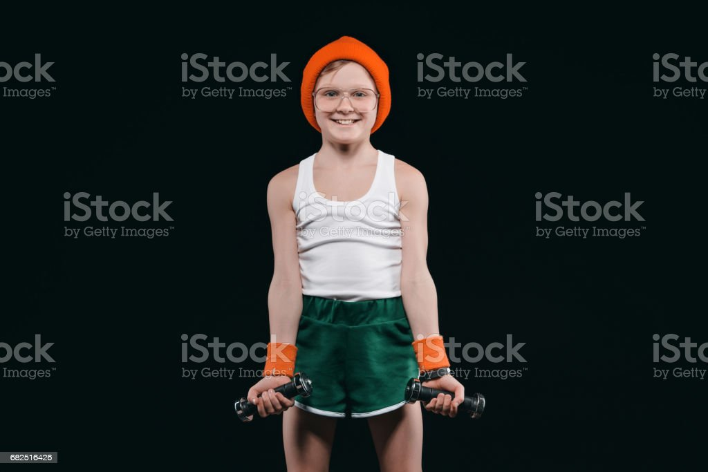 boy training with dumbbells isolated on black. athletics children concept foto stock royalty-free
