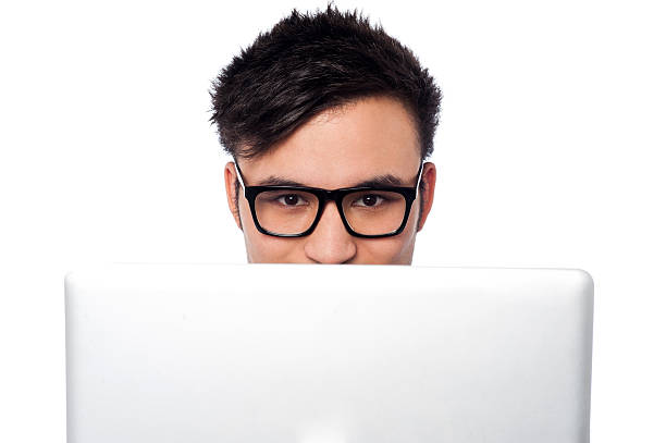 Boy trying to hide his face behind laptop stock photo