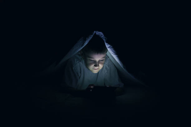 junge unter blaket mit tablet - bett für jungs stock-fotos und bilder