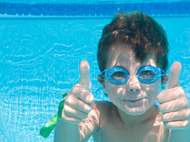 Boy Underwater In Swimming Pool With Thumbs Up. stock photo