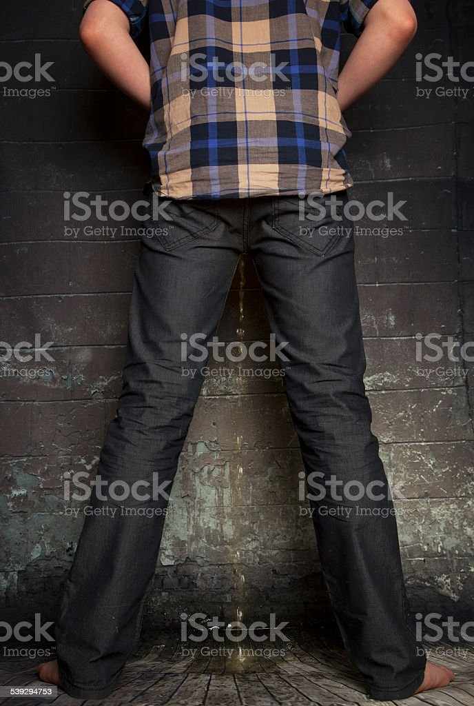 Boy urinating against the wall. stock photo