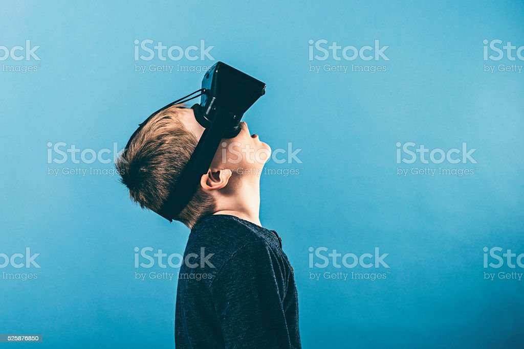 Boy uses VR glasses and looks up stock photo