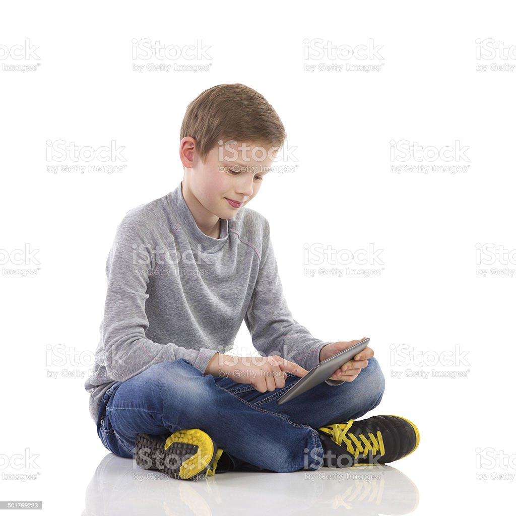 Petit garçon à l'aide d'une tablette numérique. - Photo