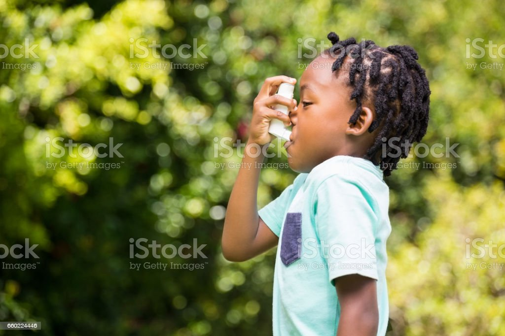 Boy using an asthma inhaler stock photo