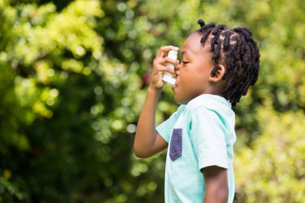 Boy using an asthma inhaler stock photo