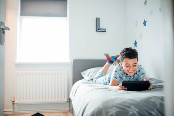 junge mit digital-tablette am morgen - bett für jungs stock-fotos und bilder
