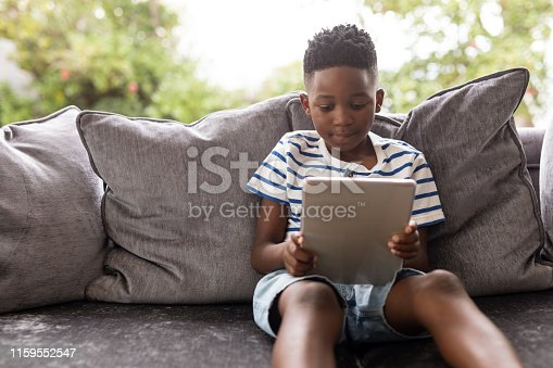 Front view of African american Boy using digital tablet on a sofa in living room at home