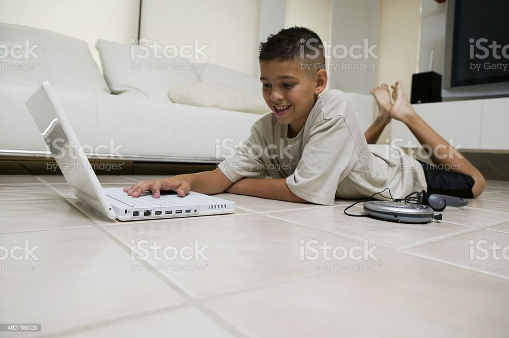 Boy Using Laptop on Floor stock photo