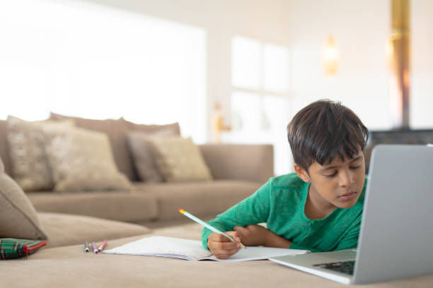 Boy using laptop while drawing a sketch on book at home stock photo