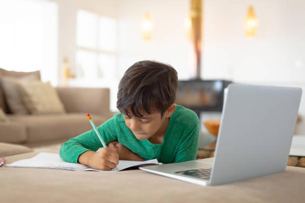 Junge mit Laptop beim Zeichnen einer Skizze auf Buch zu Hause – Foto