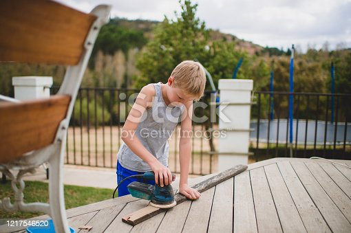 A young blond hair Boy is carefully using an orbit sander to clean a wooden plank from a bench he is renovating.  He is sanding the wooden piece of wood down.  It is an electrical orbit sander with a blue colour. He is using a wooden deck as a workbench in the backyard.