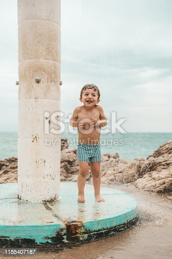 Boy using shower at the beach
