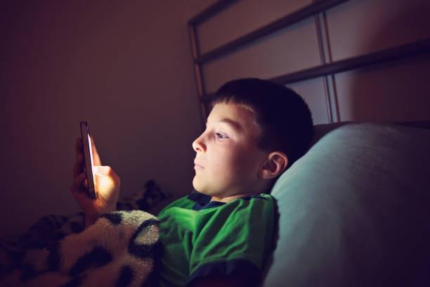 junge mit smartphone in der nacht - bett für jungs stock-fotos und bilder