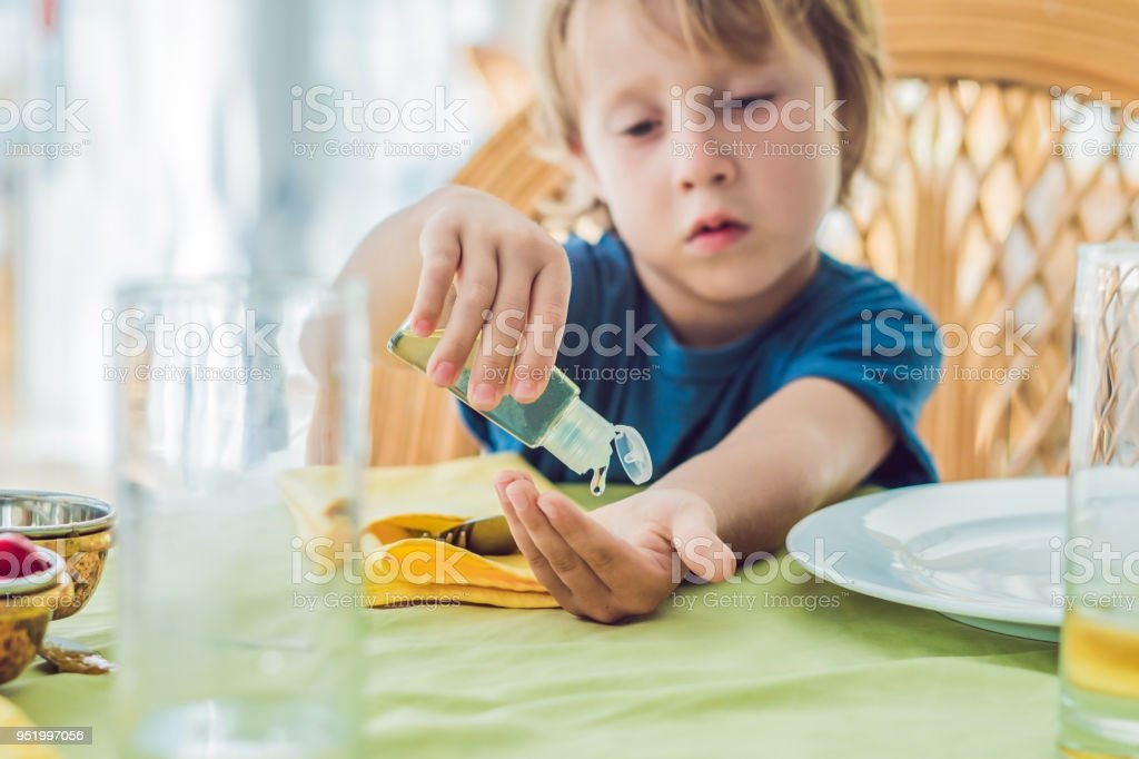 Boy using wash hand sanitizer gel in the cafe stock photo