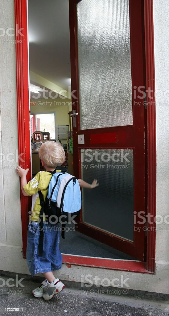 A boy waiting at a door for the first day of kindergarten stock photo