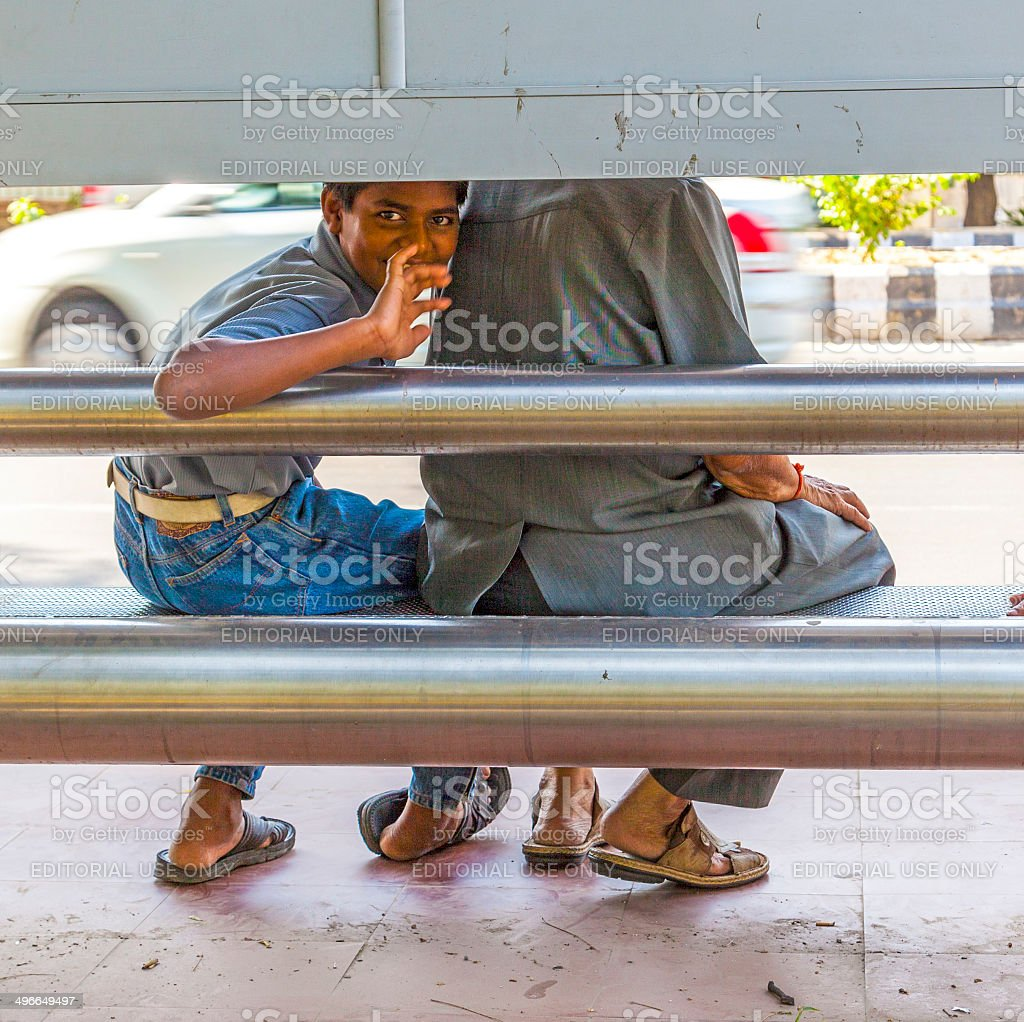boy waits for the bus in Delhi, India stock photo