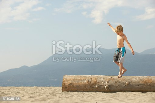 620402800istockphoto Boy walking across a log on the beach 521035138