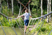 This photo shows a pre-teen boy balancing on a rope bridge that is part of an obstacle course in a park.  This was taken in the evening of a late summer day.