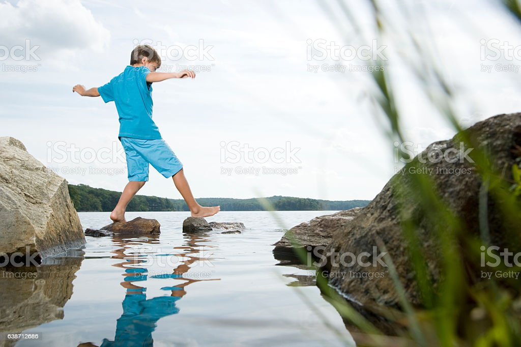 Boy walking barefoot across stones in lake stock photo