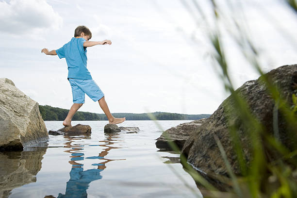 Boy walking barefoot across stones in lake Boy walking barefoot across stones in lake stepping stock pictures, royalty-free photos & images