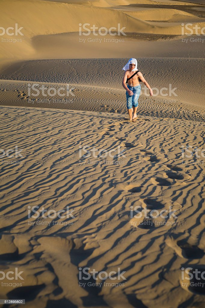 boy walking through sandy dunes royalty-free stock photo
