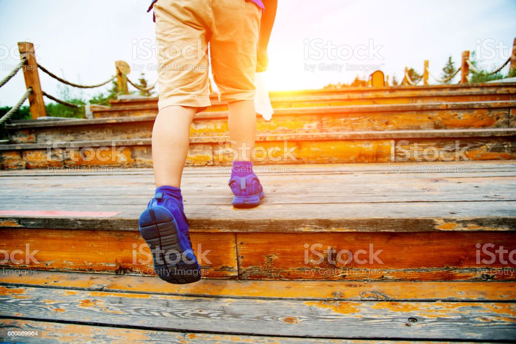 Boy walking upstairs outdoors stock photo