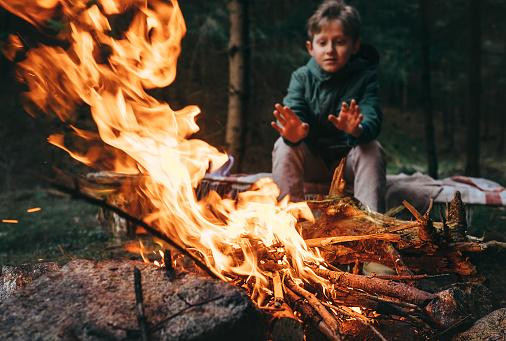 少年は近くにキャンプファイヤーの手を温め - 1人のストックフォトや画像を多数ご用意 - iStock