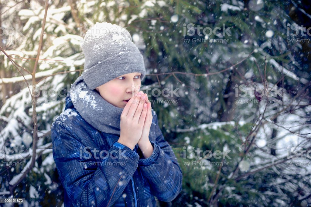 A boy warms his hands from the cold in winter stock photo