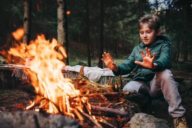 junge wärmt seine hände in der nähe von lagerfeuer im wald - kindergrill stock-fotos und bilder