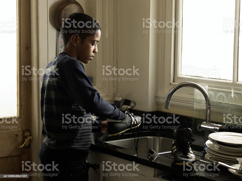 Boy (12-13) washing sport shoes in kitchen sink royalty-free stock photo