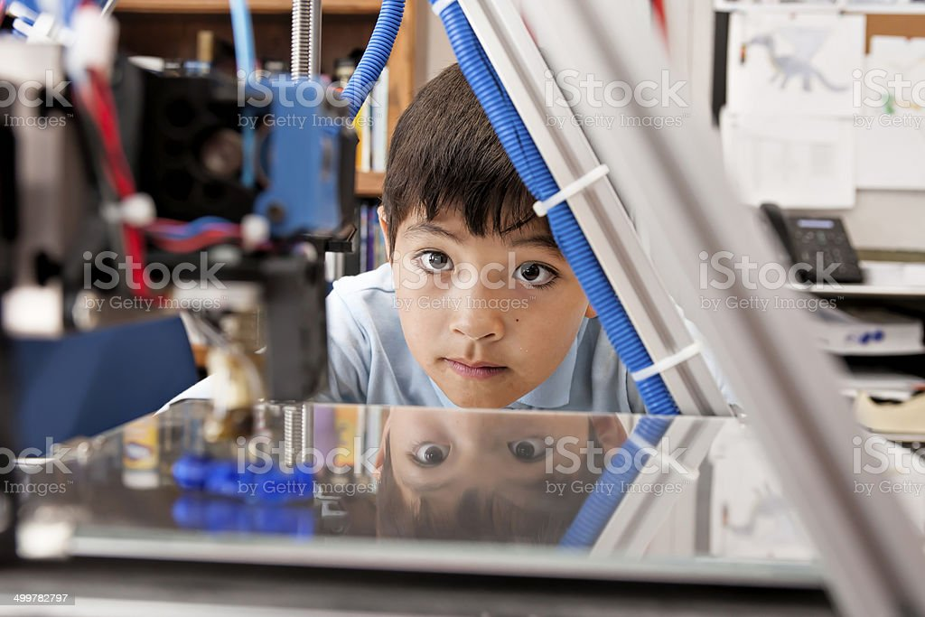 Boy watches machine intently. stock photo